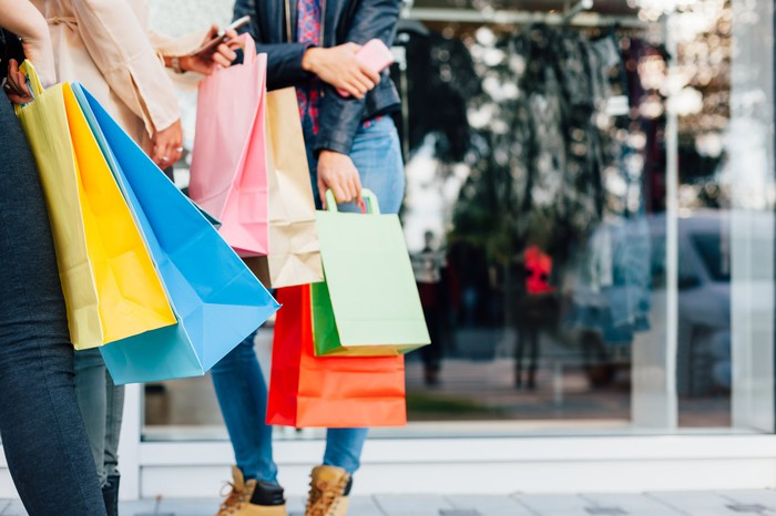 People carrying multi-colored shopping bags.