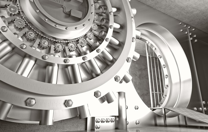 An open and massive bank vault door in silver tone with a ramp leading into the vault.