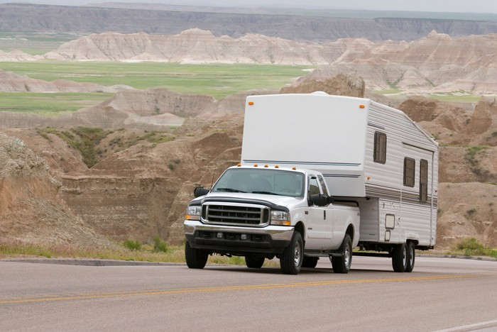 A truck tows an RV up a hill.