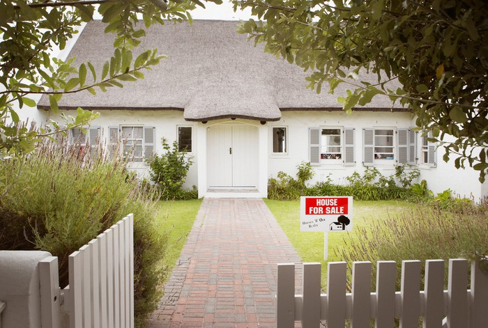 House with for sale sign on front lawn