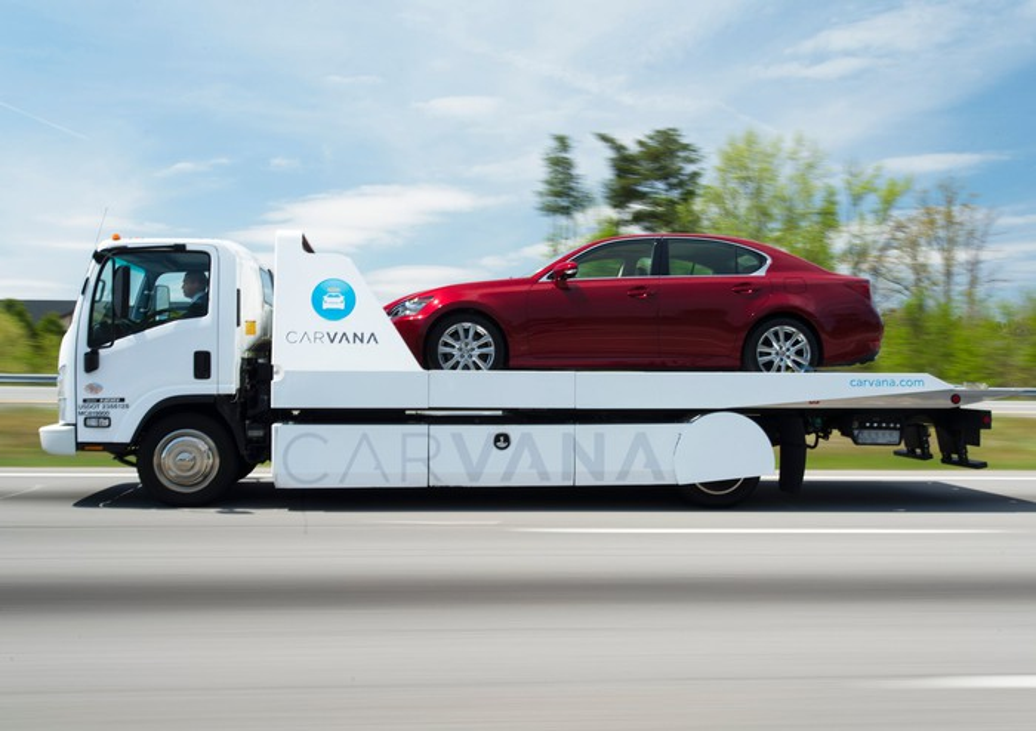 Car on the back of a Carvana trailer.