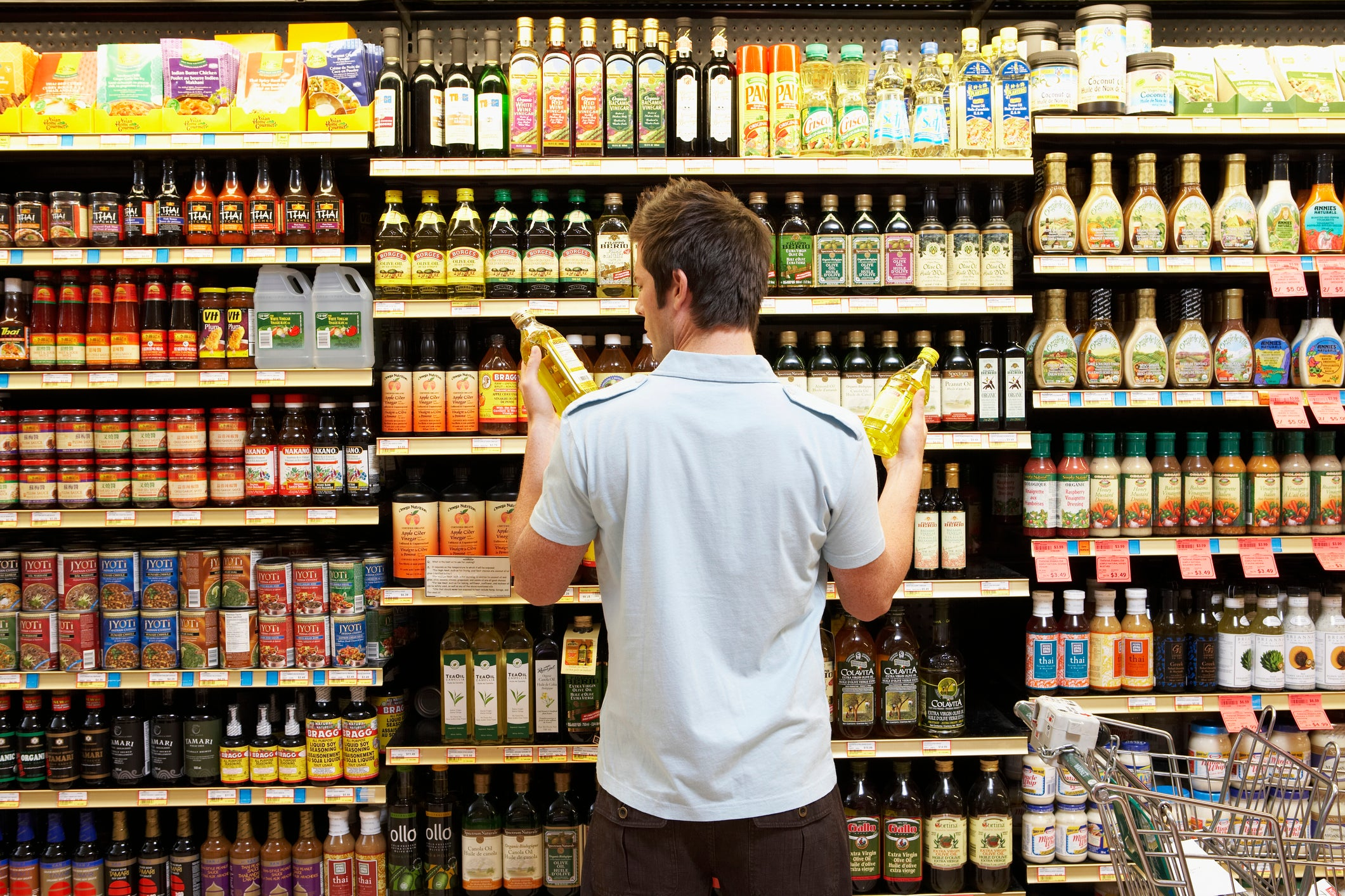 Man in grocery retail store deciding between two things to buy