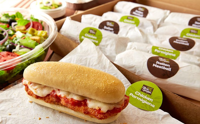 A spread of Olive Garden catered sandwiches and a salad.