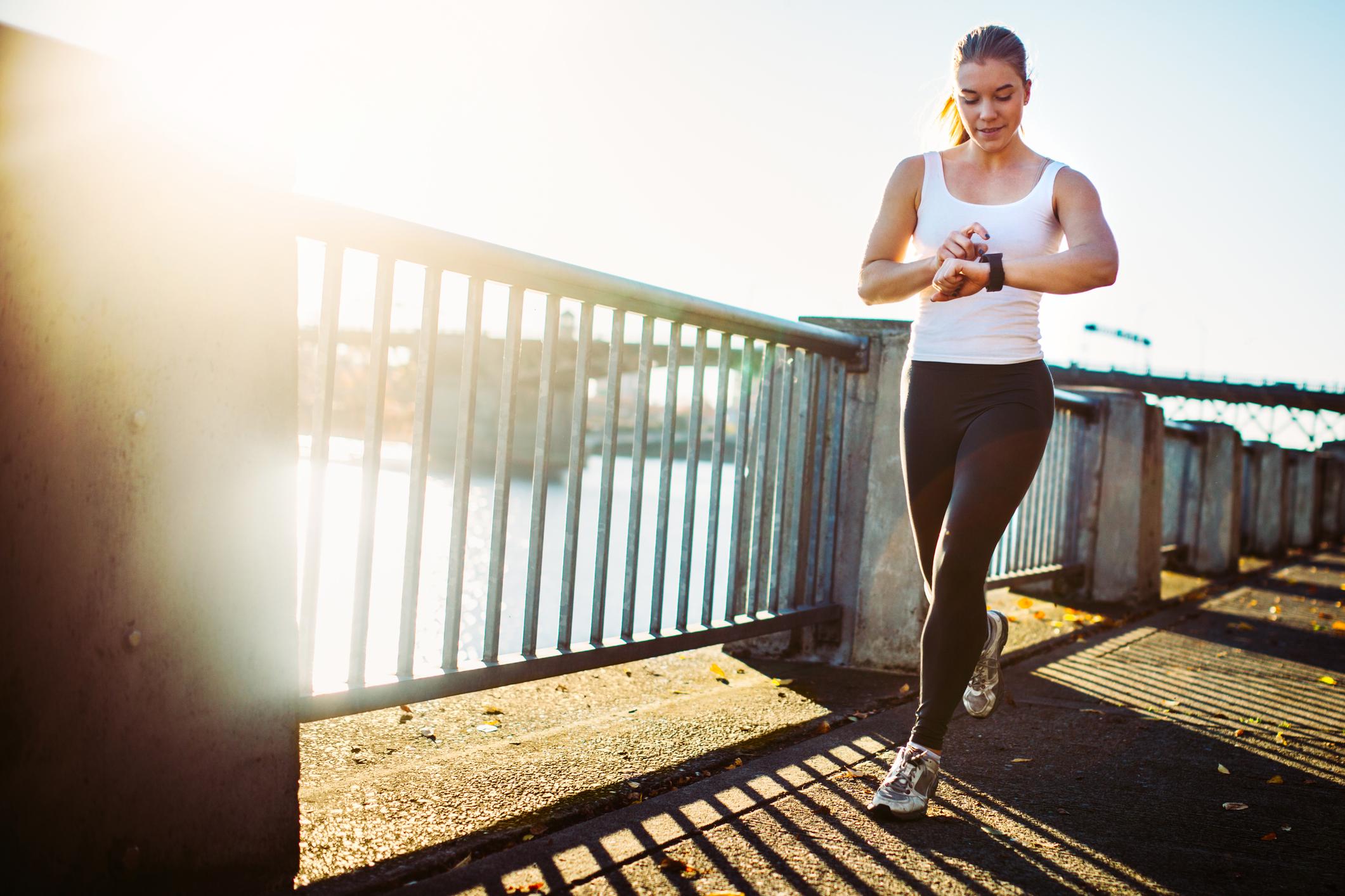 A jogger checks her smartwatch.