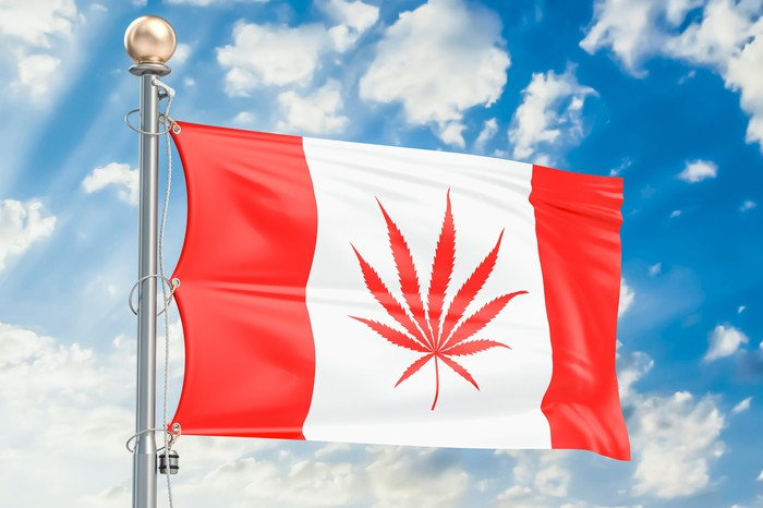 A Canadian flag on a flag pole with the maple leaf replaced by a marijuana leaf.