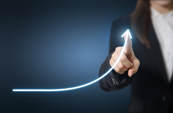 Woman in business suit drawing a line with her finger indicating exponential gains