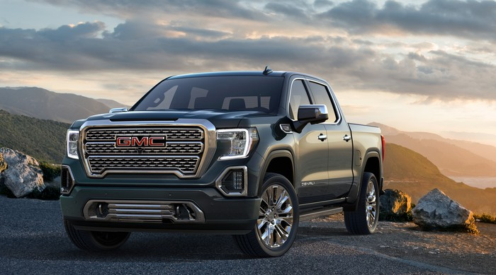 A 2019 GMC Sierra Denali, a large pickup, in a rural setting.