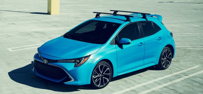 A blue 2019 Toyota Corolla hatchback, a small sporty-looking four-door car, photographed from above in a sunny parking lot.