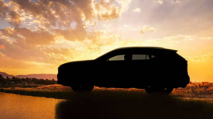 "A ""teaser"" image showing the 2019 RAV4 in shadow, parked by a lake."