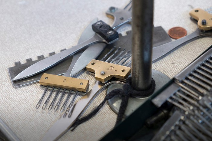 Shears and various fabric tools on a flat surface at a Canada Goose production facility.