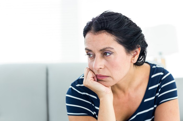 A woman, seated, looks away unhappily with her chin resting on her hand.
