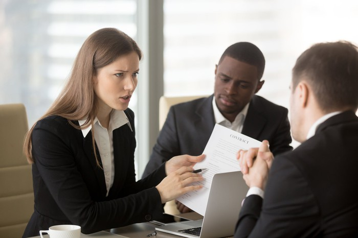 In an office setting, people in business attire review a contract, with a woman pointing to the document with a look of concern.