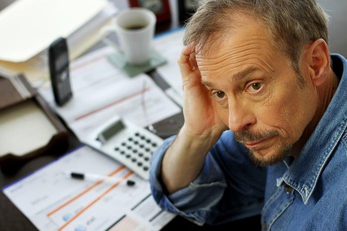 A worried man examining his finances.