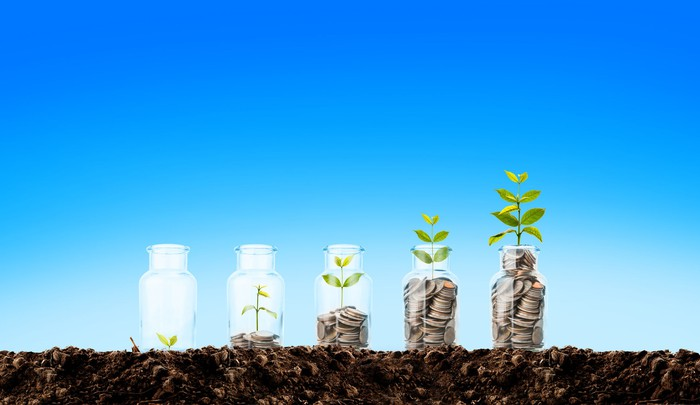 Jars with progressively larger piles of coins and a growing plant.