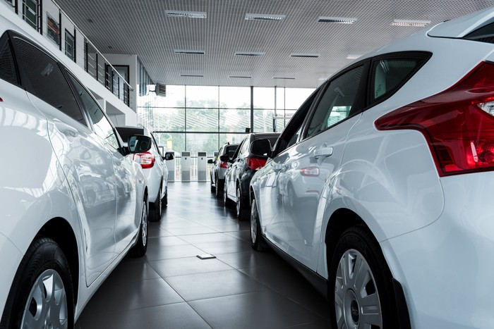 The inside of a vehicle showroom with two white vehicles on display.