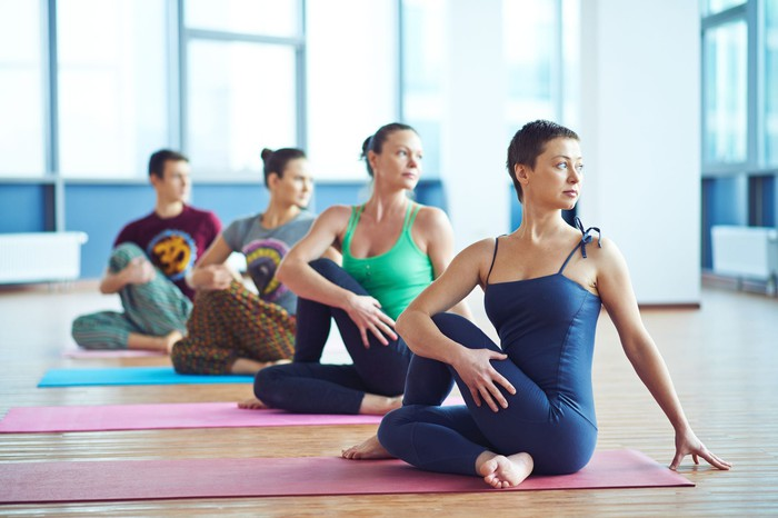 People in a yoga class stretching in a brightly lit room.