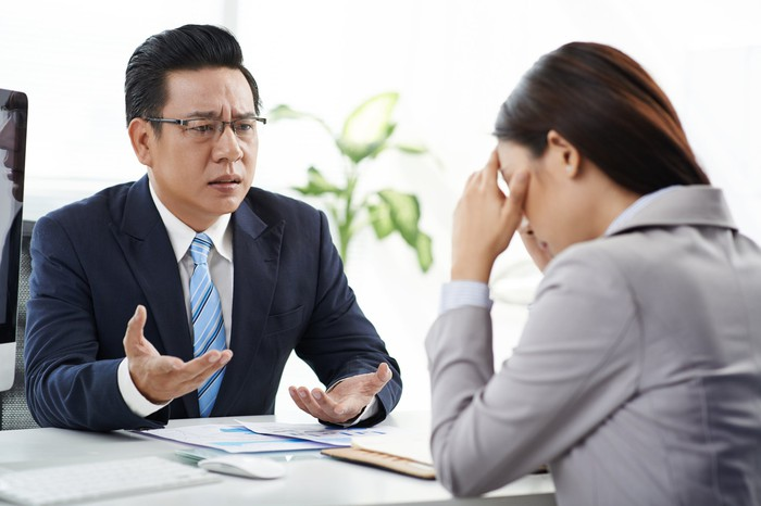 Man in suit gesturing toward woman in suit sitting across from him and holding her head as if crying