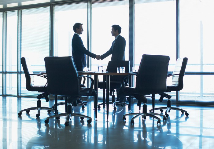 Two people in suits shaking hands in a conference room.