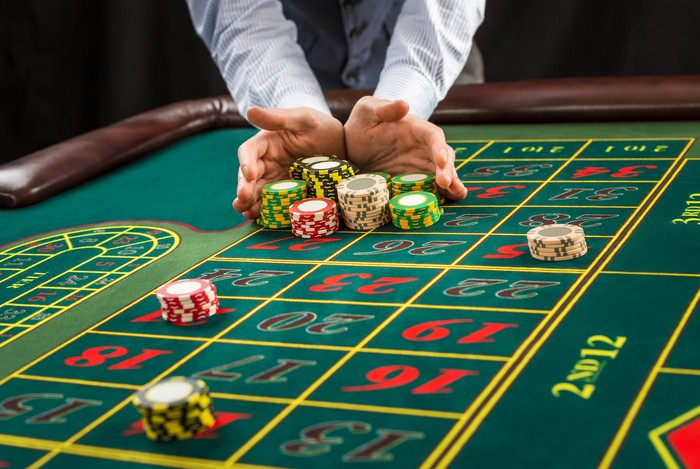 A dealer collects chips on a roulette table.
