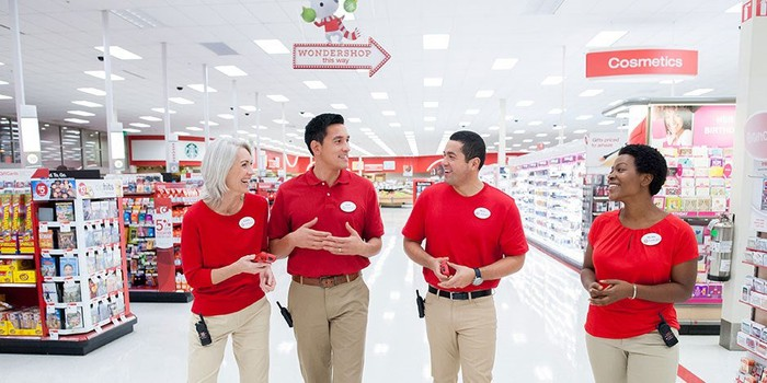 Four Target employees walking down an aisle in a Target store.