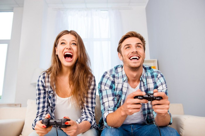 A smiling man and woman playing video games.