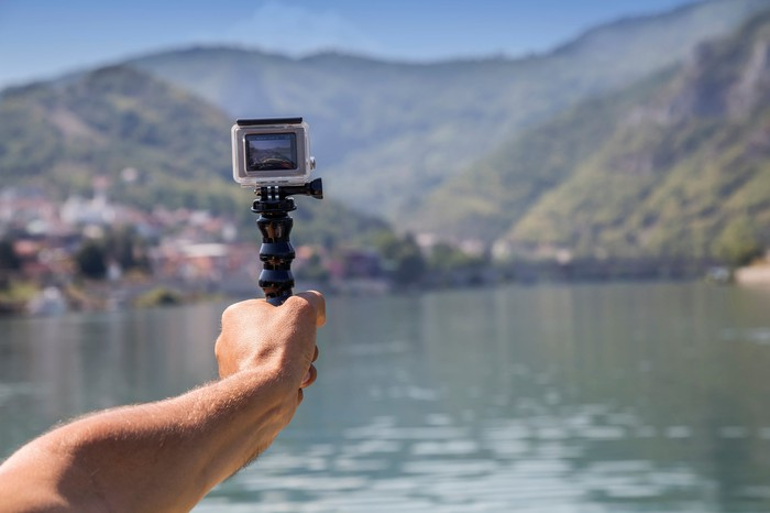 A person holding a GoPro camera in their outstretched hand on the water.