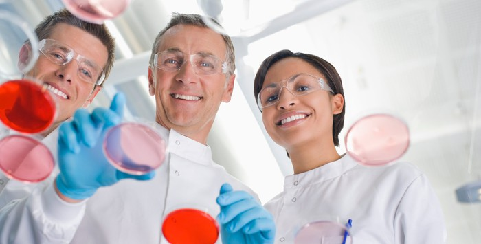 Scientists smile as they work with petri dishes.