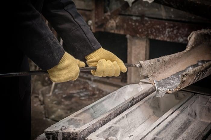 A person pouring liquid aluminum into ingot molds