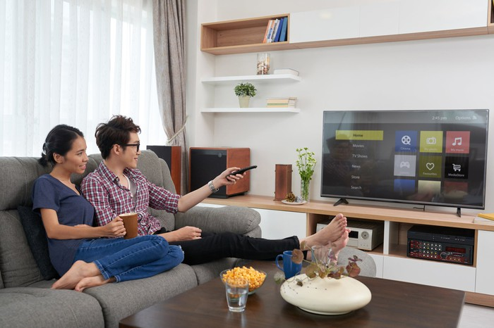 A couple sitting on a couch choosing an app to watch on a smart tv.