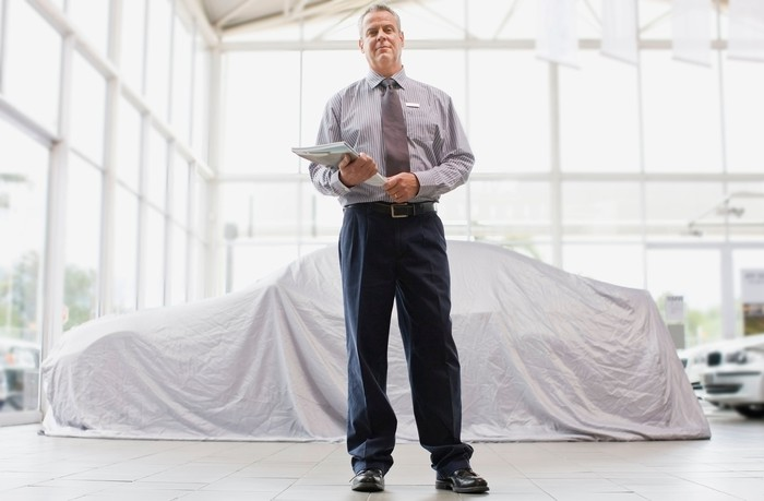 A car salesman standing on a showroom floor holding a folder with papers.