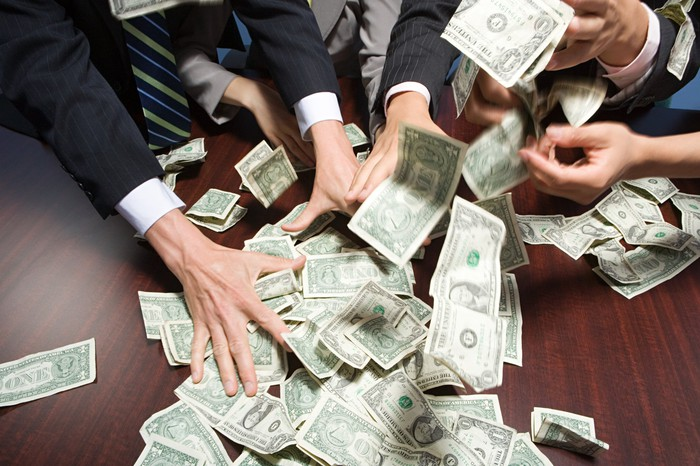 People in business attire grabbing cash scattered on top of a table