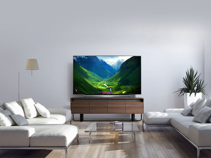 A modern living room with a big screen LG OLED TV on an entertainment stand.