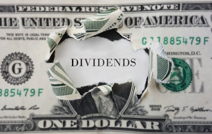 """Dollar bill with center torn out and the word """"dividends"""" showing through."""