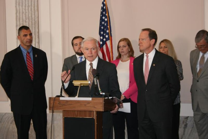 Jeff Sessions, surrounded by six men and women, speaking at a podium and addressing an audience.