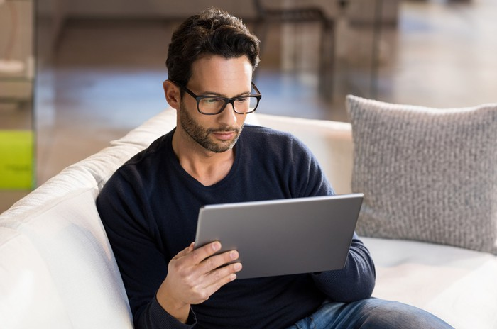 Man using a tablet on a couch