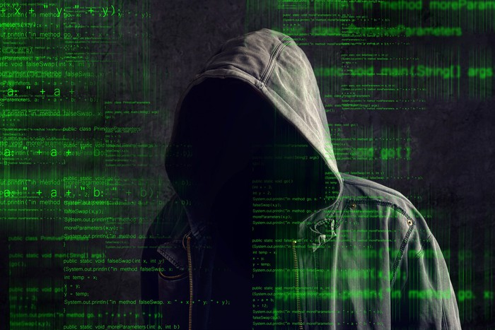 A shadowy figure in a dark hoodie, behind computer code shown in green text