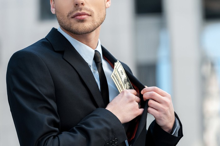 A businessman stuffs cash into the pocket of his suit coat