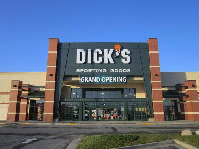A new Dick's Sporting Goods store as viewed from the parking lot. A grand opening banner hangs from the entrance.