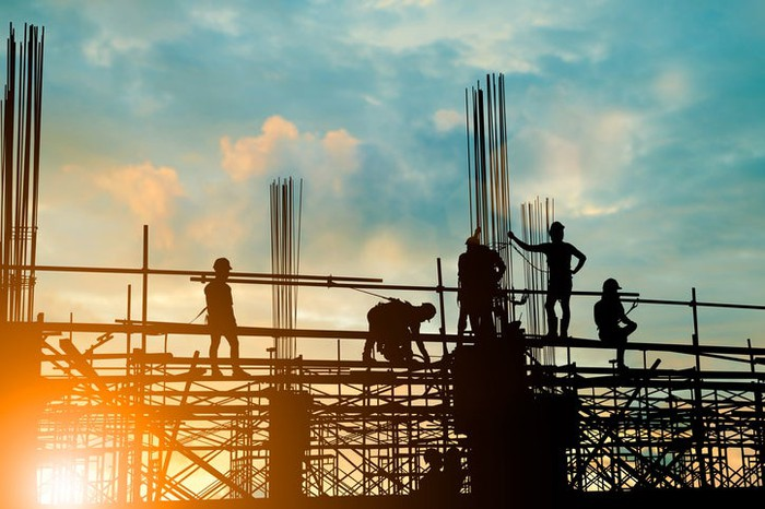 A silhouette of construction workers building a large facility.