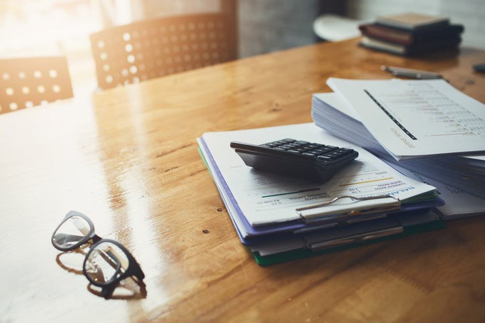 Paperwork, a calculator, and reading glasses on a desk.