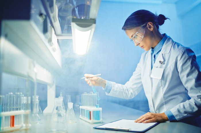 Female scientist in lab examining test tubes