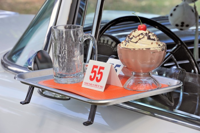 A tray golding an empty glass and a bowl of pudding on a car window at a drive-in.