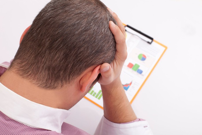 A man looking down at charts and graphs with his right hand on the side of his face.