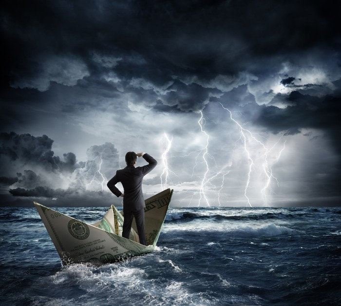Man in suit standing on a paper boat made out of a dollar bill in a stormy sea