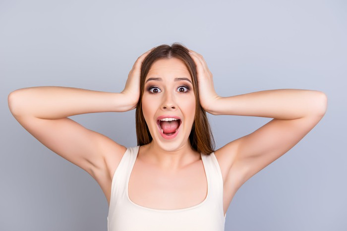 Woman with hands over ears screaming