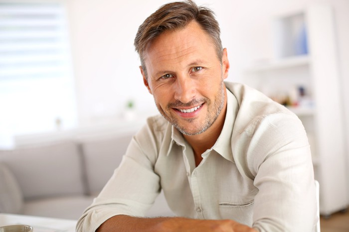 Smiling man in a white button-down shirt sitting in a white living room