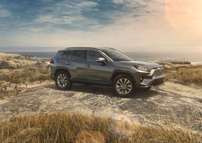 A dark silver 2019 RAV4 in a rocky field.