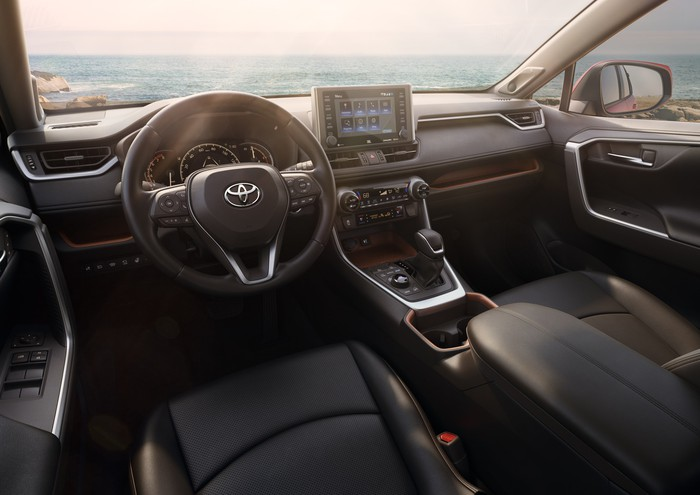 A view of the 2019 RAV4's front seats and dash, showing black leather trim with brushed-metal accents.