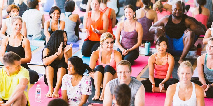 Group of men and women sitting on mats at a yoga class.