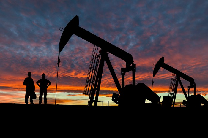 A silhouette of two people near some oil pumps at sunset.